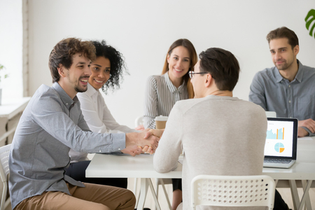 Two smiling businessmen or project team members shaking hands at multiracial group meeting, new male business partners starting collaboration at negotiations, investor and startupper making deal
