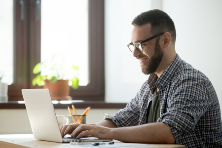 Foto de Happy male office worker smiling typing message at laptop, chatting with friends, writing positive email or consulting client online. Concept of laugher, positive work atmosphere, help and assistance - Imagen libre de derechos