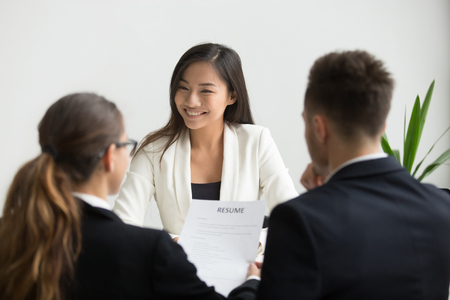 Foto de Confident millennial asian applicant smiling at job interview, happy beautiful chinese candidate or self-assured seeker being interviewed by hr managers, good performance and first impression concept - Imagen libre de derechos