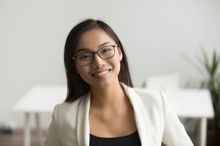 Photo pour Smiling asian woman in glasses for vision correction looking at camera, happy friendly chinese student or employee posing in office, millennial japanese woman professional head shot portrait - image libre de droit
