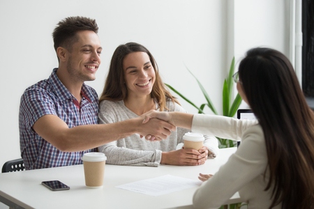 Foto de Smiling millennial couple handshaking realtor or advisor making investment deal ready to sign mortgage contract, satisfied happy customers and broker or lawyer shaking hands buying insurance services - Imagen libre de derechos