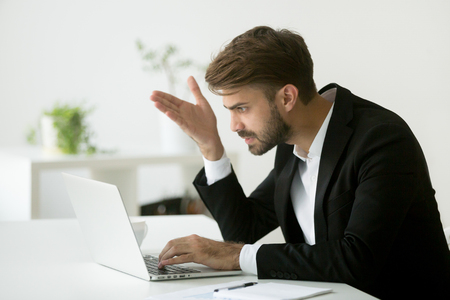 Frustrated worried businessman disappointed by negative online business news, shocked with falling sales, dissatisfied with company market failure, financial crisis, PC error. Concept of work stress