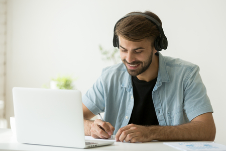 Photo pour Smiling man in headphones watching webinar, listening to web audio course, making notes and writing important information. Happy student enjoying music while taking e-learning class, remote studying - image libre de droit