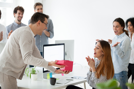 Photo for Excited male worker congratulating shocked female employee with special occasion, presenting gift box with unexpected surprise - Royalty Free Image