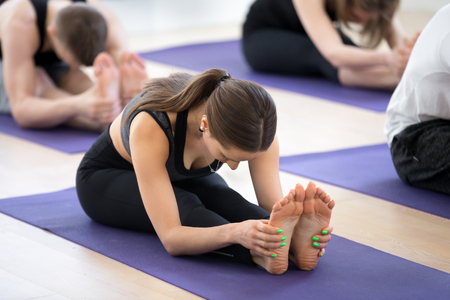 Group of young sporty people practicing yoga lesson, doing Seated forward bend pose, paschimottanasana exercise, working out, indoor full length, students training in sport club