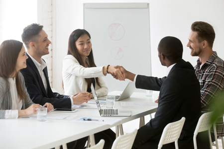 Foto de Smiling Asian female worker shaking hand of African American colleague at office business meeting, partners handshaking thanking for successful work negotiations. Concept of cooperation, partnership - Imagen libre de derechos