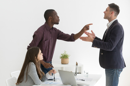 Foto de Angry multiethnic colleagues disputing during business meeting, African American worker blaming Caucasian partner for mistake, coworkers disagree on project, argue at company briefing in office - Imagen libre de derechos