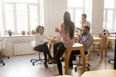 Photo for Happy multiracial workers having fun enjoying pizza together, employees spending lunch break in office talking and laughing, diverse smiling colleagues having ordered takeout meal in office chatting - Royalty Free Image