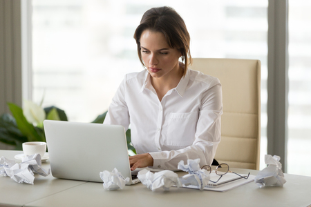 Photo pour Unmotivated businesswoman sitting at office desk with crumpled paper around trying to work at laptop, upset female employee have no inspiration, attempting to finish report or write business letter - image libre de droit