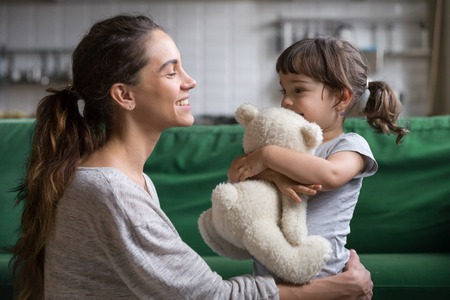 Photo pour Smiling mother hugging cute little girl holding teddy bear toy showing love and care in family, young mom embracing protecting child, sincere relationships between mum and daughter cuddling concept - image libre de droit