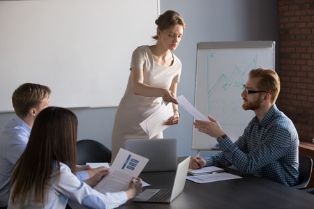 Photo for Millennial businesswoman give handout materials to work team members during flipchart presentation, female speaker or coach share documents to workers, presenter hand papers to consider or analyze - Royalty Free Image