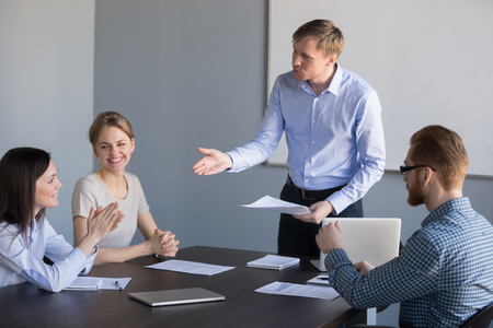 Millennial businessman talking to female worker during company briefing, complimenting for good work, male ceo greeting happy woman employee with high achievements and results at office meeting