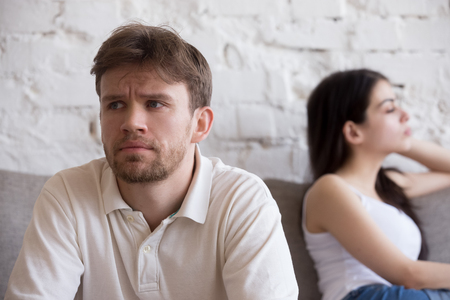 Foto de Upset millennial man think about relationship problems, having fight with proud female lover, offended couple not talking after family quarrel, sad male consider breaking up or divorce with girlfriend - Imagen libre de derechos
