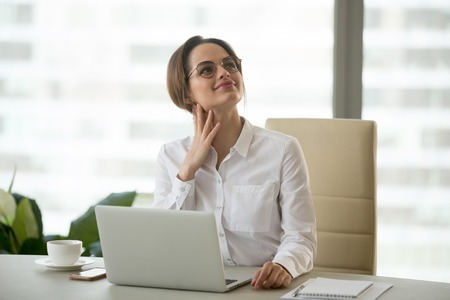 Foto de Dreamy millennial businesswoman executive thinking of future dreaming  of good career hoping for new opportunity at work, woman office employee feeling optimistic in expectation of business success - Imagen libre de derechos