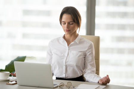 Photo pour Mindful millennial woman taking break for relaxation meditating in office to reduce work tension, calm successful businesswoman doing yoga exercises feeling zen enjoying no stress free relief concept - image libre de droit