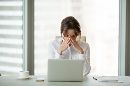 Foto de Frustrated businesswoman feels panic shock after business failure or bad news online sitting in office with laptop, stressed upset woman employee worried about bankruptcy, exhausted tired of overwork - Imagen libre de derechos