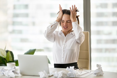 Emotional stressed businesswoman in nervous breakdown after overwork with laptop and crumpled paper, frustrated exhausted writer or office worker in panic having no ideas, block or strong headache