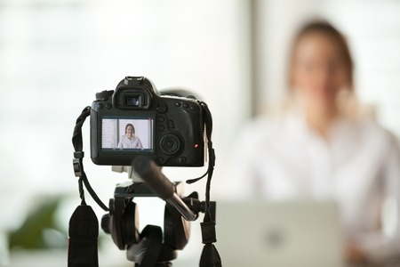Foto de Professional dslr digital camera filming live video blog interview or vlog of woman vlogger coach giving business class or presentation training people online, making videoblog and vlogging concept - Imagen libre de derechos