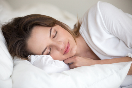 Photo pour Young woman with beautiful face sleeping well on white cotton sheets and soft pillow lying asleep in comfortable cozy bed at home or hotel enjoying healthy nap resting enough for good relaxation. - image libre de droit