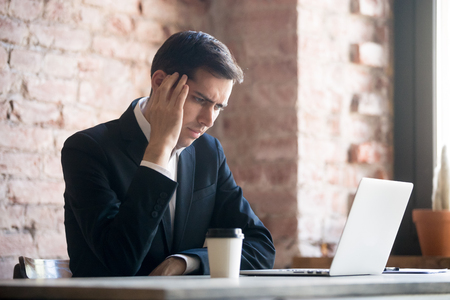 Tired businessman having a headache in office. Working at computer, touching head at work. Head pain, fatigue and overworking, coping with stress concept