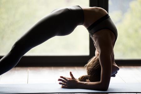 Young sporty woman practicing yoga, doing Elbow Bridge exercise, Dvi Pada Viparita Dandasana pose, working out, wearing sportswear, grey pants and top, indoor, body close up view, yoga studio