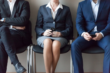 Close up business people sitting in chairs in queue waiting job interview. Candidates for one position to company. Human resources, workplace inequality, discrimination based on person gender concept