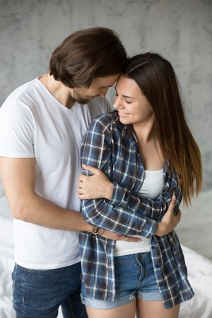 Foto de Loving affectionate man hug girlfriend from behind, romantic millennial couple embrace enjoying intimate moment together, boyfriend holding beloved girl in arms, standing touching, looking in the eyes - Imagen libre de derechos