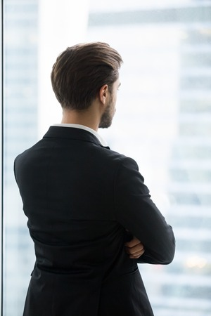Back view of thoughtful millennial businessman standing look in window thinking about career opportunities or promotion, serious male worker plan or imagine future projects. Business vision conceptの写真素材