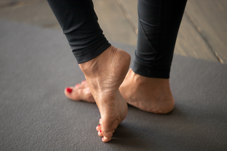 Foto de Sporty active woman practicing yoga, doing exercises to strengthen muscles in the foot, ankle, working out, wearing sportswear, indoor close up, at yoga studio - Imagen libre de derechos