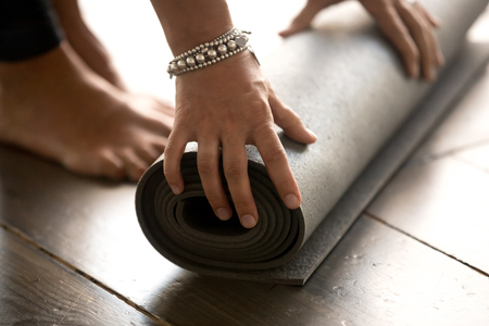 Foto de Fitness mat, equipment for sport class. Well-being concept. Girl unrolling fitness mat before or after working out in yoga studio club, at home or at gym on wooden floor. Hands and legs close up - Imagen libre de derechos