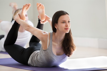 Young sporty attractive woman practicing yoga, doing Dhanurasana exercise, Bow pose, working out, wearing sportswear, black pants, top, indoor full length, yoga studio. Well-being concept