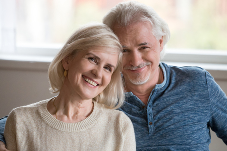 Foto de Headshot portrait of happy middle aged romantic couple dating posing indoors, smiling retired old family embracing looking at camera, loving senior mature man and woman hugging bonding together - Imagen libre de derechos
