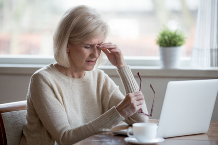 Foto de Upset fatigued overworked senior mature business woman taking off glasses tired of computer work, exhausted middle aged employee suffers from blurry vision after long laptop use, eye strain problem - Imagen libre de derechos