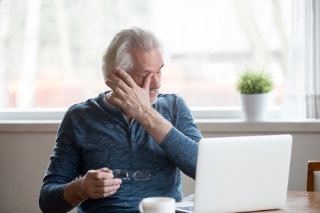 Foto de Fatigued mature old man taking off glasses suffering from tired dry irritated eyes after long computer use, senior middle aged male feels eye strain problem or blurry vision working on laptop at home - Imagen libre de derechos