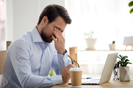 Businessman sitting at the desk in office at workplace took off his eyeglasses and rubs his eyes. Fatigue and stress at work, poor vision and influence of computer on human health, overworking concept