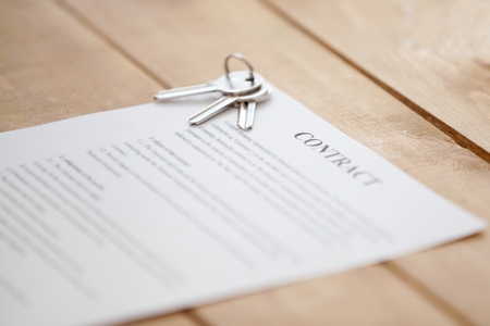 Photo pour Close up of keys lying on a contract document paper on a wooden table. New dwelling or home successful real estate deal, buying selling, renting and tenancy, mortgage and loan concept, focus on keys - image libre de droit