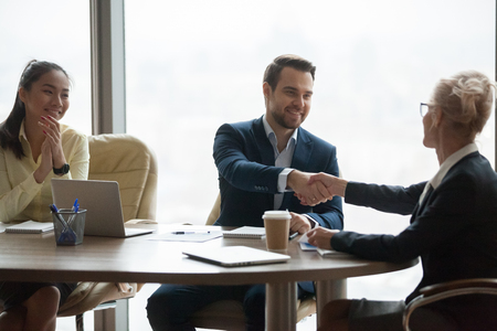 Foto de Businesswoman shaking hand of male colleague greeting him with promotion, female boss handshaking partner congratulating with closing deal or contract sign, thanking for meeting. Cooperation concept - Imagen libre de derechos