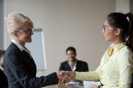 Female boss congratulate Asian employee handshaking and greeting her during meeting, happy businesswoman shake hand of woman worker complimenting with promotion or good work results. Reward concept