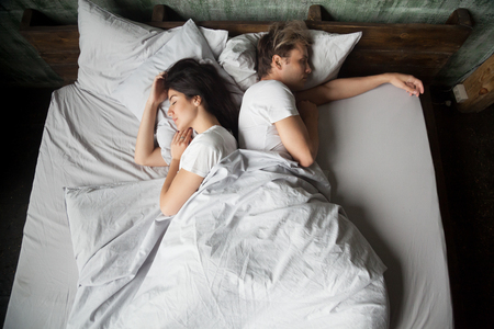 Photo pour Young girl and guy, couple sleeping under blanket with their backs to each other in bed in bedroom at home, top view. Early morning, lazy Sunday weekend or day napping. People relaxing resting at home - image libre de droit