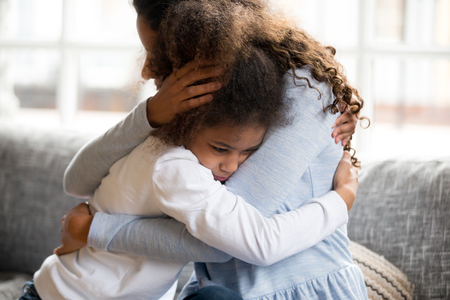 Photo pour Black African mother embrace little preschool frustrated kid sitting on couch together at home. American loving mother supports disappointed daughter sympathizing, making peace after scolding concept - image libre de droit