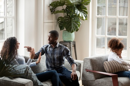 Photo pour Black family with little preschool daughter in living room at home. Wife and husband sitting on couch and quarrelling. Sad frustrated child sitting on armchair feels unhappy Break up in family concept - image libre de droit