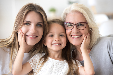 Portrait of three generations of women look at camera posing for family picture, cute little girl hug mom and granny enjoy time at home, smiling mother, daughter and grandmother spend weekend together