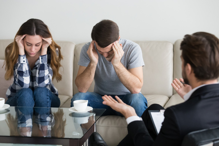 Depressed frustrated couple family touching head at meeting with psychologist counselor. Emotional breakdown, feels exhausted, desperate, unhappy. Problems in family, distress, distrust, break up