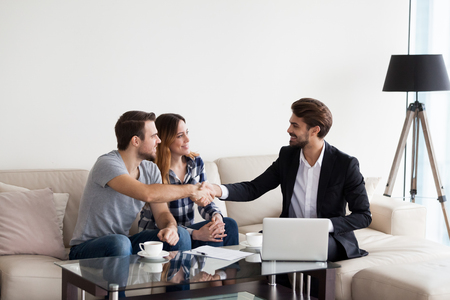 Photo pour Young couple, family at meeting with realtor, interior designer, decorator, landlord making deal. Husband handshaking with man in suit. Concept of meeting with client, customer - image libre de droit