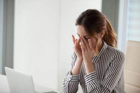 Foto de Tired young woman massaging nose bridge at workplace. Businesswoman experiences discomfort from long work at computer. Bad eye vision concept - Imagen libre de derechos