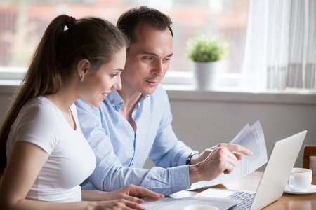 Foto de Happy positive millennial spouses sitting at the desk at home read notice paper check bills or bank account balance feeling happy and glad. Couple have income or last loan payment good news concept - Imagen libre de derechos
