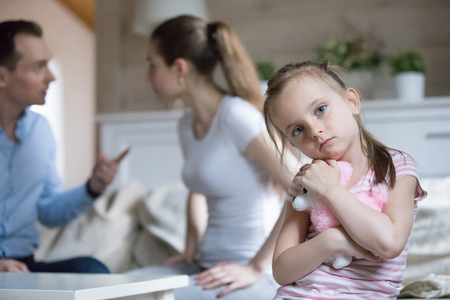 Photo pour Unhappy married couple and small child at home. Angry husband and wife quarreling arguing talking aloud, focus on sad frustrated little daughter suffers embrace toy looking at camera. Break up concept - image libre de droit
