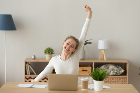 Happy satisfied young woman sitting at the desk in office room or home at workplace finish work, stretching out with raised hands. Millennial female relaxing after working hard day, no stress concept