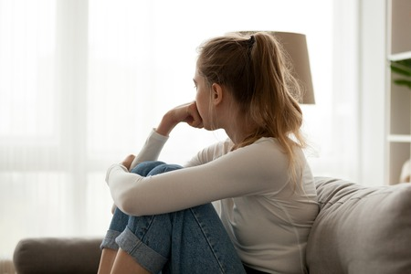Foto de Side view young woman looking away at window sitting on couch at home. Frustrated confused female feels unhappy problem in personal life quarrel break up with boyfriend or unexpected pregnancy concept - Imagen libre de derechos