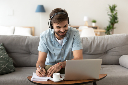 Photo pour Man sitting on couch in living room at home enjoying studying using laptop and headset looking at device screen listening audio making some notes. Male has lesson online e-learning in internet concept - image libre de droit
